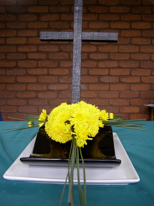 Garden party arrangement: As we gather at the foot of the Cross, we, as God's people, become the Light of the World. As symbolized by the bright yellow radiating flowers.